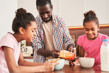 Father Lovingly Imposes Granola Or Flakes At The Plates To His Daughters