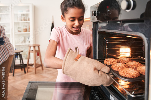 Canvas-taulu Girl taking tray with cookies out of the oven while baking at the kitchen