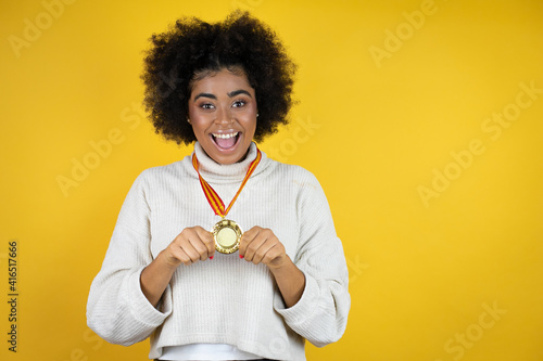 Obraz African american woman wearing casual sweater over yellow background holding a medal with a happy face standing and smiling with a confident smile showing teeth - fototapety do salonu