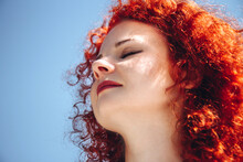 Face Of Young Beautiful Woman Close-up. Female With Curly, Red Hair, Eyes Closed Against The Blue Sky. Bright Woman Outside The House. Casual Life Of A Young Lady. Lifestyle