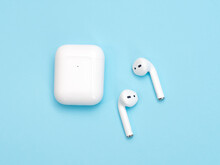 Wireless Earphones On The Blue Background. Bluetooth Technology