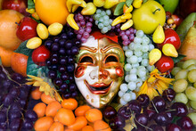 Smiling Carnival Mask Surrounded By Appetizing Fruits.