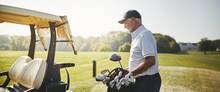 Senior Man Putting His Golf Club Bag On A Cart