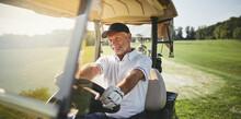 Smiling Senior Man Driving His Golf Cart On A Fairway