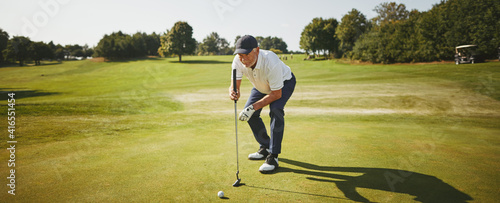 Fototapeta Senior man preparing to putt on a golf green obraz