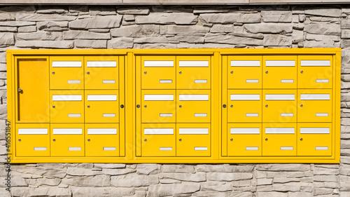 Obraz na plátně Boites aux lettres jaunes sur un mur en pierre
