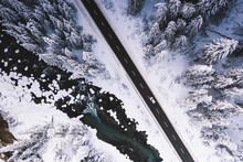 Car Traveling On Snowy Mountain Road Across Frozen River And Woods, Aerial View, Switzerland, Europe