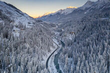 Sunrise Over Winding Mountain Road And Frozen River In The Forest Covered With Snow, Zernez, Graubunden Canton, Switzerland, Europe