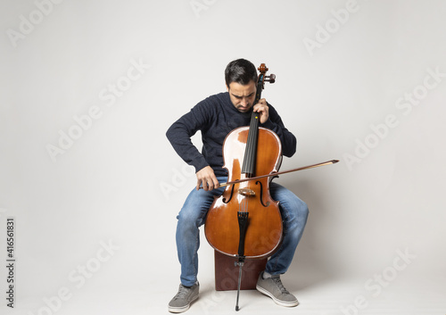 Billede på lærred young man playing cello on the white background