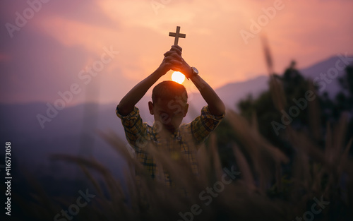 Christian boy standing holding a Cross overhead for pray and worship to God with light sunset background, beliefs of children concept Fototapete
