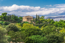 Athens Greece Temple Of Hephaestus Day View Surrounded By Greenery On A Bright Sunshine Over Puffy Clouds.