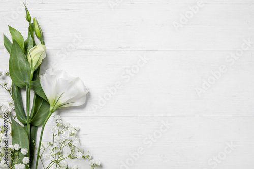 Beautiful flowers on white wooden background, flat lay. Space for text