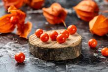 Physalis On Wooden Stump. Ripe Berries Of Autumn Red Physalis Fruit. Berries Fruit. Physalis Or Chinese Lantern Plants