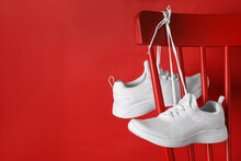 Stylish Sneakers With White Shoe Laces Hanging On Chair Against Red Background. Space For Text