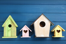 Beautiful Bird Houses On Blue Wooden Table, Flat Lay