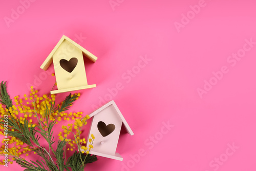 Beautiful bird houses and mimosa flowers on pink background, flat lay. Space for text