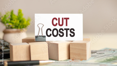 Photo piece of paper with the text: CUT COSTS, business and finance concept