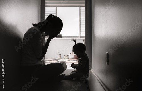 Fotografia Sad and tired mother ant home alone with child.