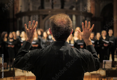 Photo Musician leads a choir during a concert in a cathedral