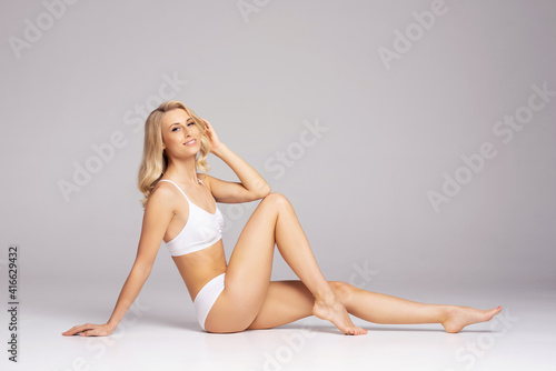 Fototapeta Young, fit and beautiful blond woman in white swimsuit over grey. Healthcare, diet, sport and fitness concept. obraz