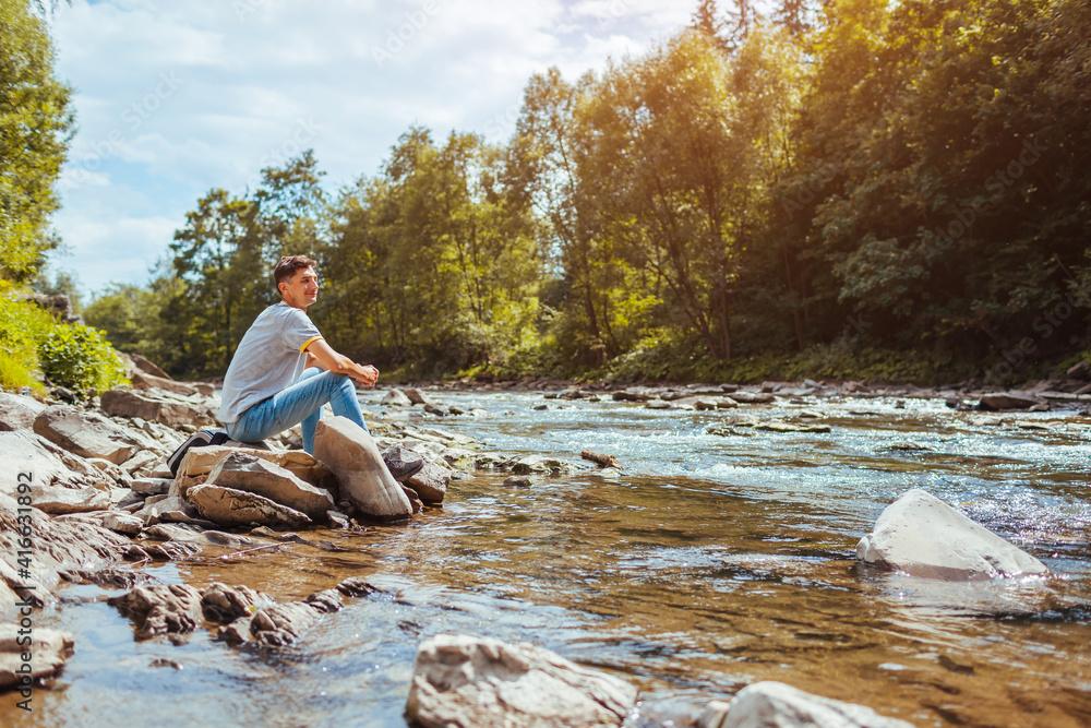 Fototapeta Young man relaxing by mountain river enjoying natural landscape. Traveler backpacker sitting on rock. Summer trip