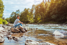 Young Man Relaxing By Mountain River Enjoying Natural Landscape. Traveler Backpacker Sitting On Rock. Summer Trip