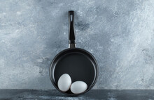 Black Frying Pan With Two Organic Chicken Eggs Over Grey Background