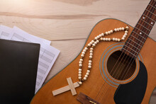 Acoustic Guitar With Religious Songbook On Wooden Table Top View