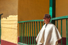 Portrait Of A Farmer Rests Next To An Old Colonial House In The Main Park Of Sora In Boyacá, Colombia