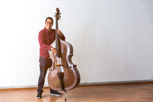 Professional Double Bass Player. Photo Shooting In Studio. White Background