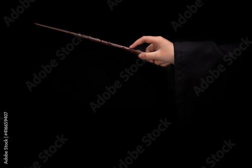 Fotografija Magic wand stick, Teens hand holding a wand wizard conjured up in the air