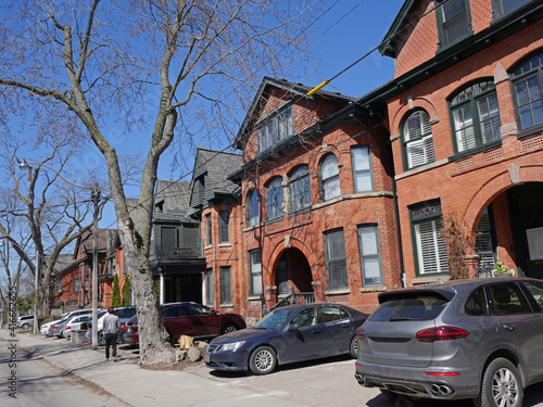 Fototapeta premium Urban gentrified street with old Victorian houses and parking allowed on front pavement.