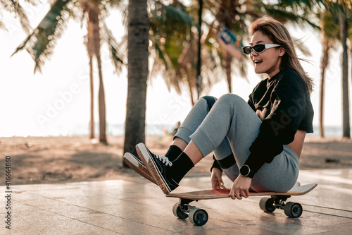 Photo Close-up,Asian women surf skate or skates board outdoors on beautiful summer day