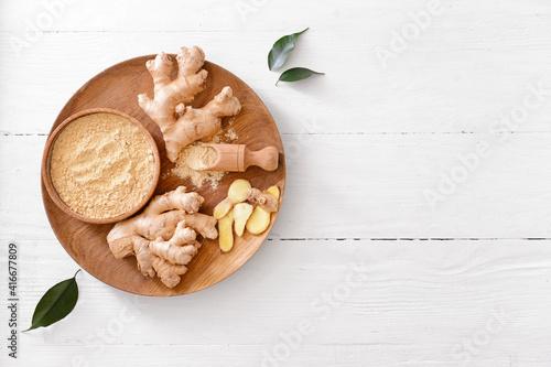 Fototapeta Bowl with ginger powder on light wooden background