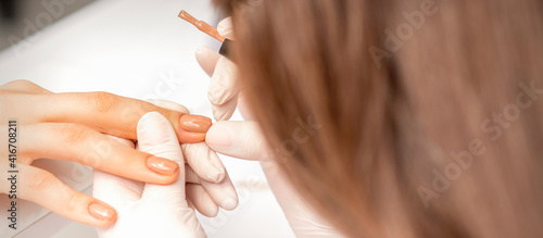 Canvas Print Manicurist applying beige nail polish on fingernails of a female client in a nai