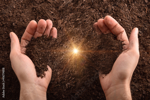 Fotografie, Obraz Hands with dirt and glitter in center with ground background