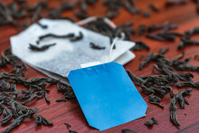 A New Tea Bag With A Label Close-up Lies On The Leaves Of A Large-leaved Black Tea