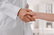 Doctors greeting woman with handshake in clinic, closeup