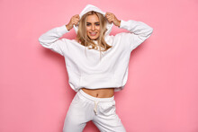 Sexy Blonde Woman Wear Of White Set Of Tracksuit Isolated On Pink Pastel Background