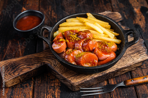 Fototapeta Currywurst Sausages with Curry spice on wursts served French fries in a pan. Dark wooden background. Top view obraz
