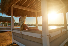 Woman Sitting At Cabana With Straw Roof On A Sandy Beach On Sunset