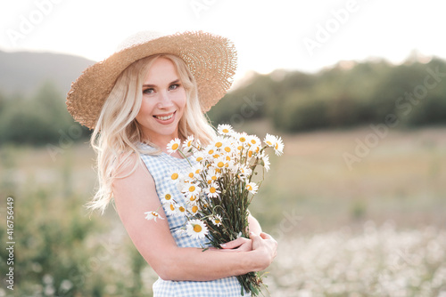 Smiling beautiful blonde woman 25-29 year old holding bouquet of fresh daisy wearing straw hat and dress posing in meadow close up Fotobehang