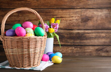 Colorful Easter Eggs In Wicker Basket And Tulips On Wooden Background. Space For Text