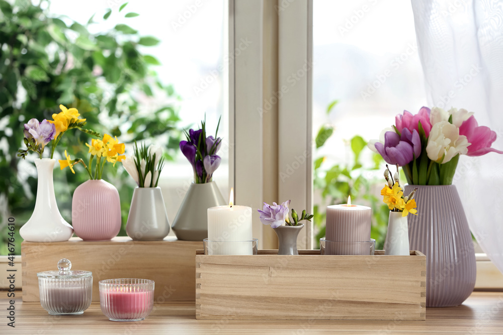 Fototapeta Beautiful spring flowers with burning candles on window sill