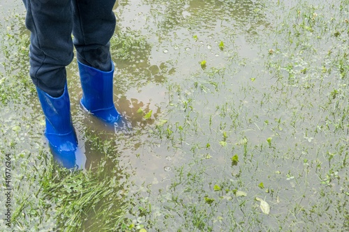 Canvas Print The child stands in the garden in the water, feet in rainfoot