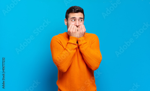 Canvas Print handsome adult blond man looking worried, anxious, stressed and afraid, biting f