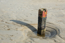 Weathered Beach Pole With A Red Head In A Hole On The Beach Worn Out By The Water