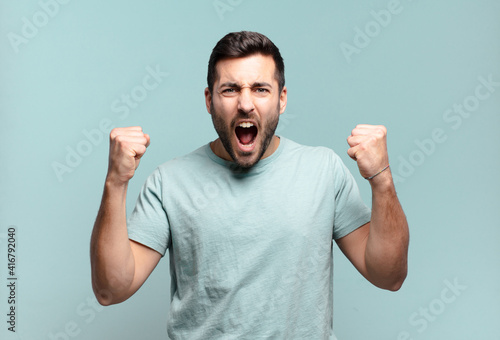 Fototapeta young handsome adult man shouting aggressively with an angry expression or with fists clenched celebrating success obraz