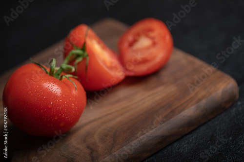Stampa su Tela Close up photo of whole or half cur ripe tomato on wooden board