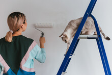A Girl Of Asian Appearance Makes Repairs In The House With A British Cat. Young Woman Paints The Wall White, The Shetland Tabby Cat Sits On The Stairs.